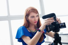 Woman Recording Vlog Video Blog Using DSLR Camera. Happy girl at home setting video camera and attaching lens to dslr. People and technology, young woman working Royalty Free Stock Images