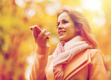 Woman recording voice on smartphone in autumn park. Season, technology and people concept - beautiful young woman in autumn park and using voice command recorder royalty free stock photography