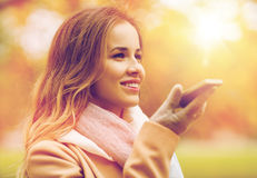 Woman recording voice on smartphone in autumn park. Season, technology and people concept - beautiful young woman walking in autumn park and using voice command stock photo