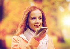 Woman recording voice on smartphone in autumn park. Season, technology and people concept - beautiful young woman walking in autumn park and using voice command stock image