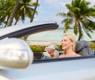 Woman recording voice on smartphone at car. Road trip, technology and travel concept - happy young woman calling on smartphone or using voice command recorder at royalty free stock photos