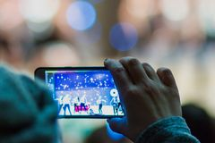A woman records a video or photographs the performance of artists on stage using her phone. Hand close-up. Blurry. Bokeh. Copyspac stock image