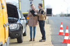 Woman with recovery driver beside road Stock Image