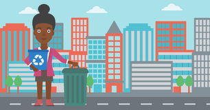 Woman with recycle bins. An african-american woman standing with a recycle bin in hand and another bin on the ground on a city background vector flat design stock illustration