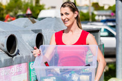 Woman on recycling center throwing bottles in container Royalty Free Stock Images