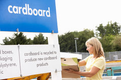 Woman At Recycling Centre Disposing Of Cardboard. Smiling Stock Image