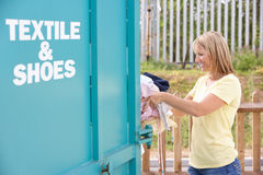 Woman At Recycling Centre Disposing Of Clothing Stock Photography
