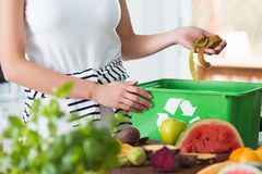 Woman composting organic kitchen waste. Woman recycling organic kitchen waste by composting in green container during preparation of meal Royalty Free Stock Photos