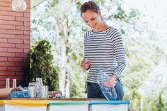 Woman recycling plastic bottle. Satisfied activist woman putting a plastic bottle into special recycling container in the garden stock images