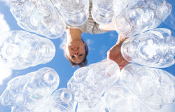 Woman recycling plastic water bottles high key. Looking up POV in New Zealand, NZ Stock Photo
