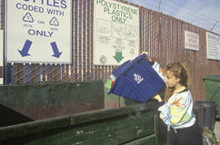 A woman recycling plastics. In separate recycling containers at the Santa Monica Recycling Center, CA Stock Image