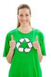 Woman in recycling symbol t-shirt gesturing thumbs up. Smiling young woman in recycling symbol t-shirt gesturing thumbs up over white background Stock Photo