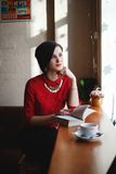 Woman in Red 3/4 Sleeve Button Up Shirt Leaning on Brown Wooden Table Top Near White Ceramic Mug during Daytime Royalty Free Stock Images