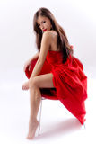Woman in red. Brunette woman in red dress sitting on a red chair Royalty Free Stock Photo