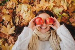 Woman with red apple in autumn park. Season, fruit and people concept - beautiful girl lying on ground and autumn leaves. Female model has fun in the fall Royalty Free Stock Image