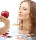Woman with red apple in water royalty free stock image