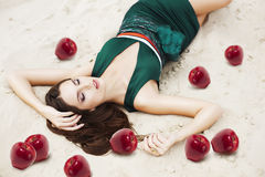 Woman with red apples on the sand Stock Images