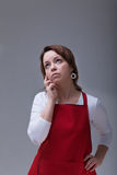 Woman in red aprons thinking Royalty Free Stock Images
