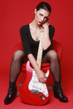 Woman on Red Background With Electric Guitar Royalty Free Stock Photos