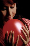 Woman with red balloon. Sensitive Woman with red balloon on black background Stock Image