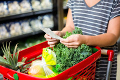 Woman with red basket holding list. In supermarket Royalty Free Stock Photography
