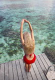 The woman in a red bathing suit is going to dive into the sea Stock Images