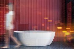 Woman in red bathroom interior with tub. Woman walking in interior of minimalistic bathroom with red and black walls, concrete floor and large comfortable white royalty free stock images