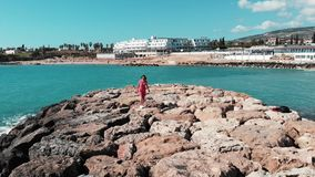Woman in red beautiful dress walking alone on rocky pier at coral bay cyprus with hotel and beach on background. Blue sea waves hi. Tting rocky beach with white stock video