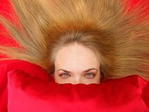 Woman on Red Bed. Blonde attractive woman laying down with hair fanned out behind her, red pillow in front of her, red background stock photos
