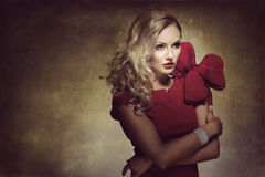 Woman in red with big bow. Blond young woman in red dress and creative hair style , looking on one side. she has a big bow stock photos