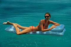 Woman in red bikini relaxing on floating device Stock Photos