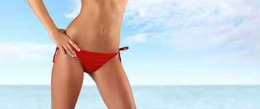 Woman in red bikini on sea and sky background Royalty Free Stock Photos