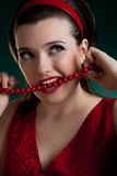 Woman in red bite the beads Royalty Free Stock Photography