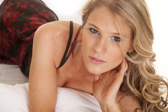 Woman red black nightgown lay forward look serious Stock Photography