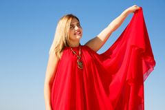 Woman in red. Blond woman in the red dress on the blue sky background Royalty Free Stock Photography