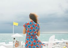 Woman in Red and Blue Floral Dress Standing Near Body of Water stock images