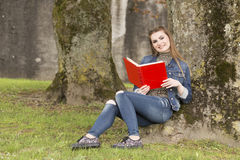 Young woman reading a red book stock images
