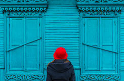 Woman in red cap looks at the blue old village house in a Russian village royalty free stock images