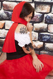 Woman red cape tattoo claw behind cape. A woman in her red hood and dress with a wolf paw print on her shoulder royalty free stock photography