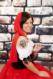 Woman red cape tattoo claw growl. A woman in her red hood and wolf paw tattoo on her shoulder growling royalty free stock photography