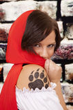 Woman red cape tattoo claw hide face. A woman hiding behing her red hood with her paw print on her arm showing stock photo