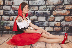Woman red cape tattoo claw legs out. A woman sitting on the ground with her wolf paw tattoo showing stock image