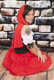 Woman red cape tattoo claw serious. A woman with a serious expression on her face in her red hood showing off her wolf paw print on her shoulder stock photography