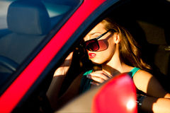Woman in red car. Woman with sunglasses get in the red  car, sunlit Stock Image