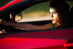 Woman in red car Stock Images