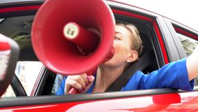 Woman in red car is sitting. She is nervous. Girl takes speaker and talk into it. Also she uses car horns. stock video footage
