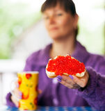 Woman with red caviar sandwich Stock Image