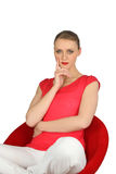 Woman in a red chair Stock Photos