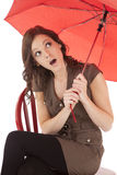 Woman on red chair look from under umbrella Royalty Free Stock Photo
