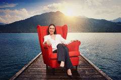 Woman on the red chair on moorage. Smiley woman resting on the red chair on moorage with beautiful landscape Royalty Free Stock Photo